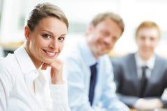 Lächelnde Frau, die bei einem Geschäftstreffen mit Kollegen sitzt Lizenzfreie Stockfotos