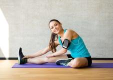Lächelnde Frau, die Bein auf Matte in der Turnhalle ausdehnt Stockfotos