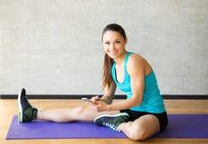 Lächelnde Frau, die Bein auf Matte in der Turnhalle ausdehnt Stockfoto