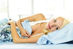 Lächelnde Frau, die in Bett legt Stockfoto