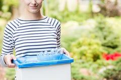 Lächelnde Frau, die blauen Behälter hält stockfotos