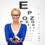 Lächelnde Frau, die Brillen trägt und hält lizenzfreies stockbild