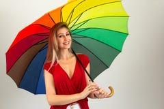 Lächelnde Frau, die bunten Regenschirm hält Blonde Person und weari Lizenzfreie Stockbilder