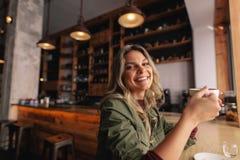Lächelnde Frau, die am Café mit Tasse Kaffee sitzt stockbilder
