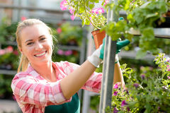 Lächelnde Frau, die in dem Garten-Center sonnig arbeitet Stockbild