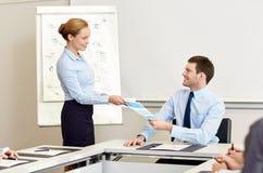 Lächelnde Frau, die dem Mann im Büro Papiere gibt Stockbild