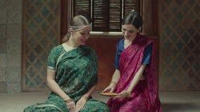 Lächelnde Frau, die dem weiblichen Gast indische Nahrung dient stock video footage