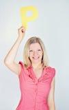 Lächelnde Frau, die den Buchstaben P hält Lizenzfreie Stockfotografie