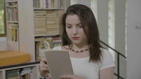 Lächelnde Frau, die in der Bibliothek genießt sich entspannt, das interessante Buchausdrücken und die Verwunderungs- und Spaßblin stock video