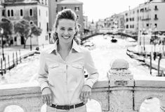 Lächelnde Frau, die an der Brücke in Venedig sich lehnt Stockfotos