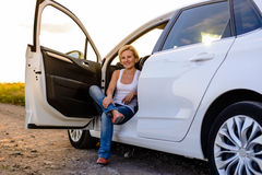 Lächelnde Frau, die in der offenen Tür ihres Autos sitzt Lizenzfreie Stockfotografie