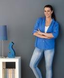Lächelnde Frau, die an der Wohnzimmerwand steht Stockfotos