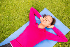Lächelnde Frau, die draußen Übungen auf Matte tut Stockfotografie