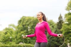 Lächelnde Frau, die draußen mit Seilspringen trainiert Stockbild