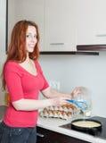Lächelnde Frau, die durcheinandergemischte Eier in der Bratpfanne macht stockbilder