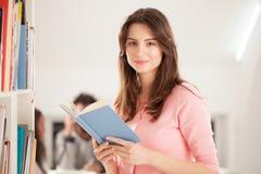 Lächelnde Frau, die ein Buch liest Stockbild