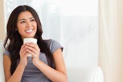 Lächelnde Frau, die ein Cup betrachtet die Decke anhält Stockfotos