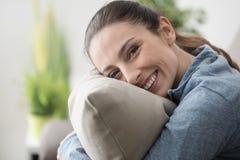 Lächelnde Frau, die ein Kissen hält stockfotos