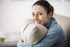 Lächelnde Frau, die ein Kissen hält lizenzfreie stockfotografie