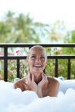 Lächelnde Frau, die ein schäumendes Schaumbad genießt Stockfotografie