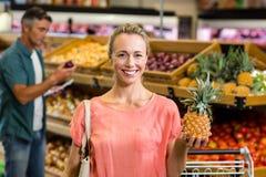 Lächelnde Frau, die eine Ananas hält Stockfotos