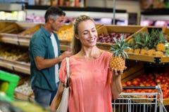 Lächelnde Frau, die eine Ananas hält und schaut Stockbilder