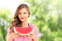 Lächelnde Frau, die eine Scheibe der Wassermelone in einem Park hält Lizenzfreie Stockfotografie