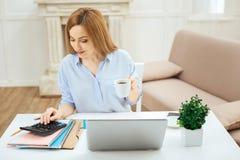 Lächelnde Frau, die eine Tasse Tee beim Arbeiten hält Stockbild