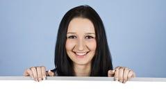 Lächelnde Frau, die eine unbelegte Fahne anhält Lizenzfreie Stockbilder