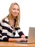 Lächelnde Frau, die an einem Laptop arbeitet Stockfotografie