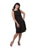 Lächelnde Frau, die in einem schwarzen Kleid steht und zur Seite schaut stockbild
