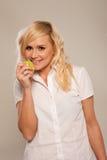 Lächelnde Frau, die einen Apfel isst Lizenzfreie Stockbilder