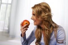 Lächelnde Frau, die einen Apfel isst Lizenzfreie Stockfotos