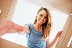 Lächelnde Frau, die einen Kartonkasten öffnet Stockbilder