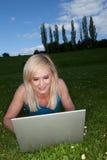 Lächelnde Frau, die einen Laptop im Park verwendet Lizenzfreie Stockfotografie