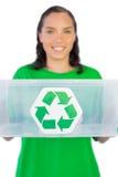 Lächelnde Frau, die einen Wiederverwertungskasten zur Kamera gibt Stockbilder