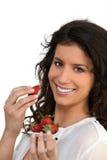 Lächelnde Frau, die Erdbeeren isst Stockfotos