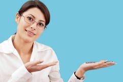 Lächelnde Frau, die etwas darstellt Stockbilder