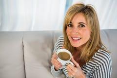 Lächelnde Frau, die etwas Tee trinkt Stockbild
