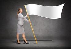 Lächelnde Frau, die Fahnenmast mit weißer Flagge hält Lizenzfreies Stockfoto