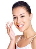 Lächelnde Frau, die Feuchtigkeitscremesahne aufträgt Stockfotos