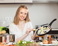 Lächelnde Frau, die Fische mit Zitrone kocht Lizenzfreies Stockfoto
