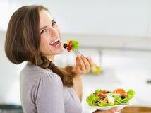 Lächelnde Frau, die frischen Salat in der Küche isst Stockfotos
