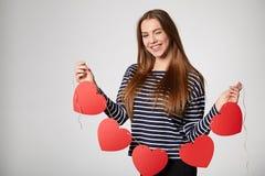 Lächelnde Frau, die Girlande von fünf roten Papierherzen hält Stockbild