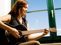 Lächelnde Frau, die Gitarre durch ein Fenster spielt Stockfoto