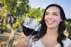 Lächelnde Frau, die Glas Wein im Weinberg mit Freunden genießt Stockfoto