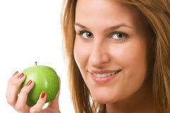 Lächelnde Frau, die grünen Apfel anhält. Stockbild