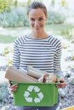 Lächelnde Frau, die grünen Behälter hält stockfotografie