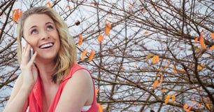 Lächelnde Frau, die Handy gegen Herbstniederlassungen verwendet Stockfotografie