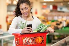 Lächelnde Frau, die Handy im Einkaufenspeicher verwendet Lizenzfreie Stockfotos